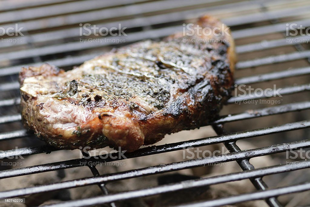 Herb crusted sirloin steak on the grill royalty-free stock photo