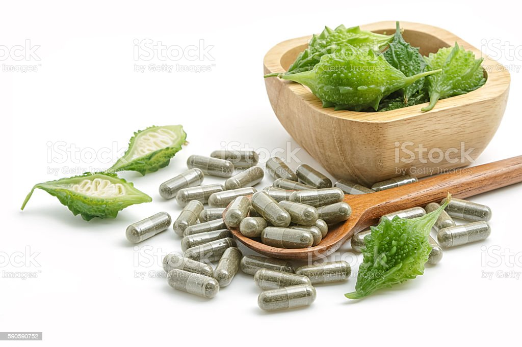 Herb pills with bitter gourd ,homeopathic medicine on white back stock photo