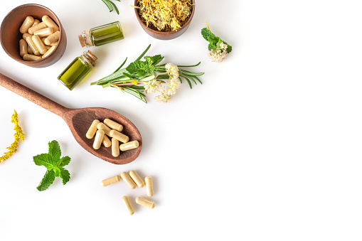 Various medicinal herbs and herbal pills isolated on white background. Top view. Copy space. Herbal medicine concept.