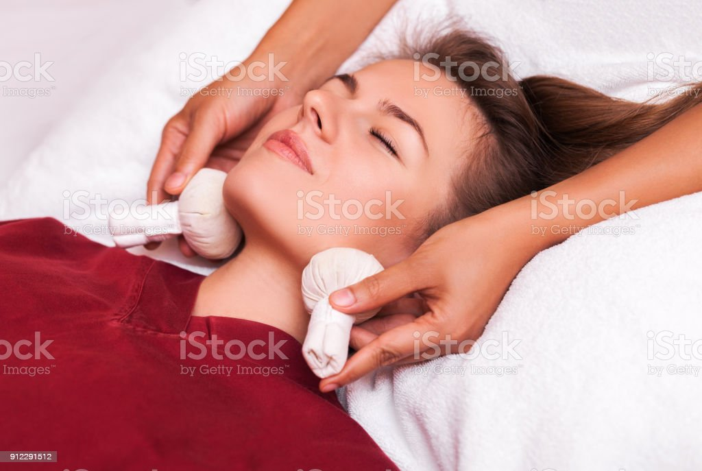 Herbal ball face massage in ayurveda spa. Female massagist with young woman in wellness center. stock photo