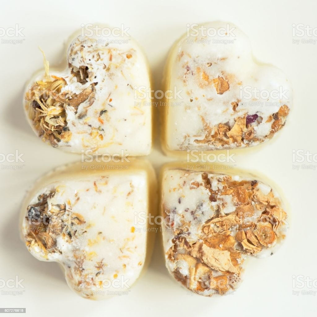 Herbal bath bombs in form of a heart on a white background. Square cut stock photo