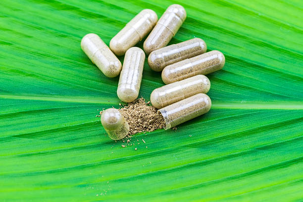 Herbal capsule and powder on green leaf  background. Herbal capsule and medicine powder on green leaf  background. antipyretic stock pictures, royalty-free photos & images