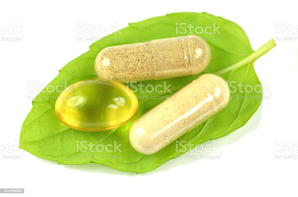 herbal capsules and fish oil capsule on mint leaf stock photo