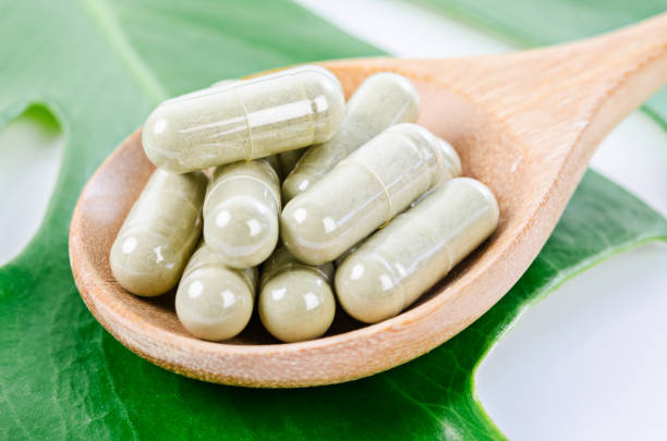 Herbal capsules from herbs in wooden spoon with green leaf for healthy. stock photo