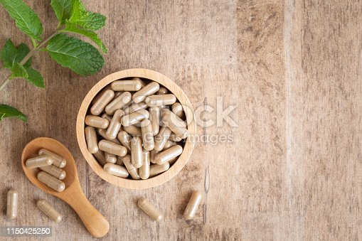 Herbal capsules  in cup on wooden table background . Top view of medicine for healthy and capsules on the spoon wooden