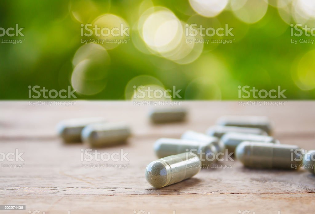 Herbal capsules on wooden table stock photo