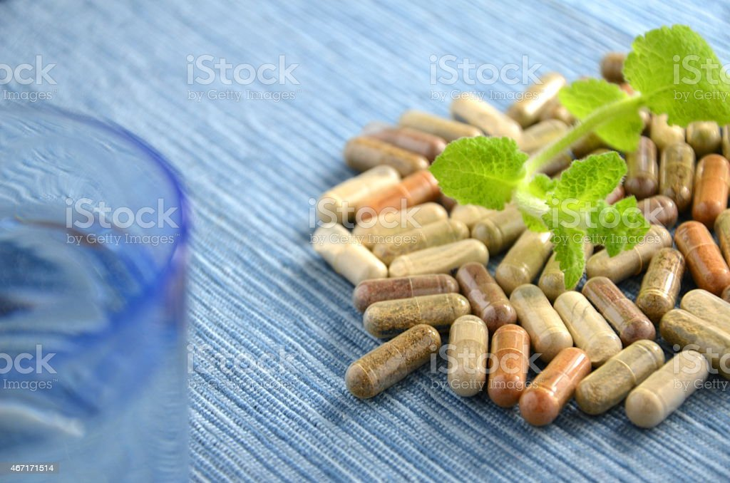 herbal capsules with mint leaves and glass of water stock photo