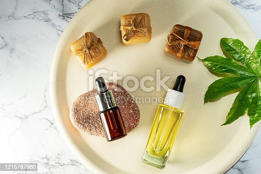 1169941952 istock photo Herbal CBD oil bottles aroma dropper on glass and hemp leaf on pastel beige plate and marble background. 1215787980