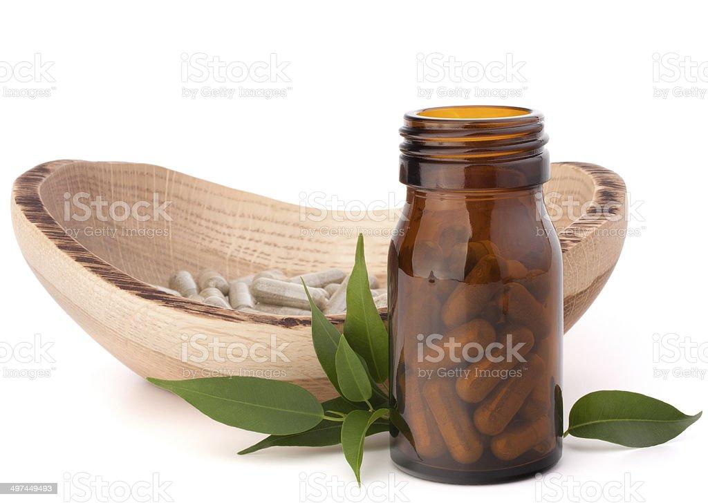 Herbal drug capsules in brown glass bottle. Alternative medicine stock photo