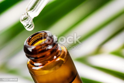 istock herbal essence. alternative medicine. essential oil dropping from pipette to the bottle 1022198458