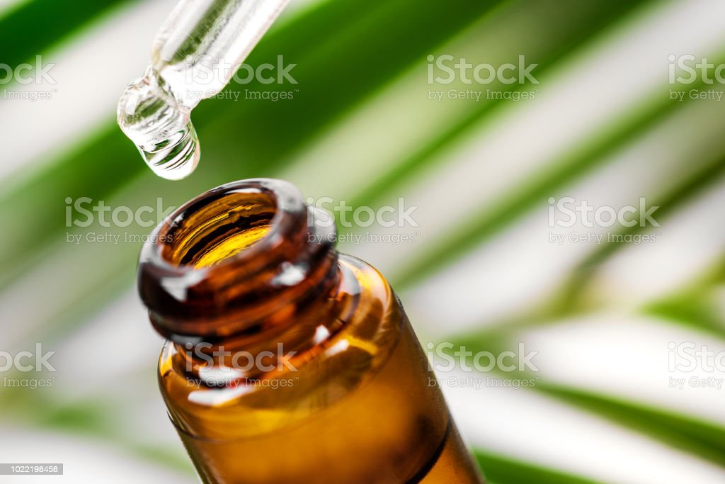 herbal essence. alternative medicine. essential oil dropping from pipette to the bottle stock photo