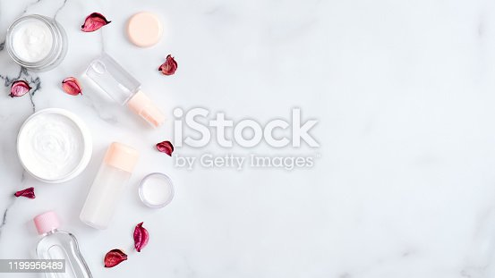 1128479585 istock photo Herbal hand cosmetic cream and lotion bottle with pink flower petals on marble background. Flat lay, top view, copy space. Hand skin care, organic beauty products concept 1199956489