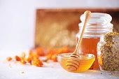 istock Herbal honey in jar with dipper, honeycomb, bee pollen granules, calendula flowers on grey background. 1176629925