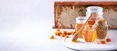 istock Herbal honey in jar with dipper, honeycomb, bee pollen granules, calendula flowers on grey background. 1176630017
