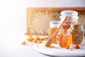 istock Herbal honey in jar with dipper, honeycomb, bee pollen granules, calendula flowers on grey background. 1176630054