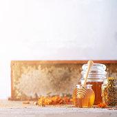 istock Herbal honey in jar with dipper, honeycomb, bee pollen granules, calendula flowers on grey background. 1176630180