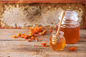 istock Herbal honey in jar with dipper, honeycomb, bee pollen granules, calendula flowers on grey background. 1176630215