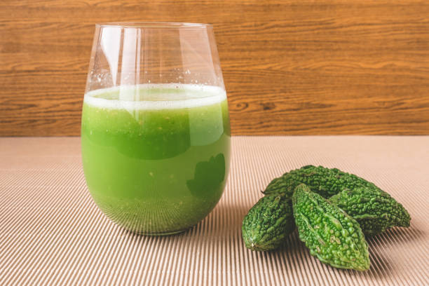 Herbal juice with bitter melon or bitter gourd on wooden background. stock photo