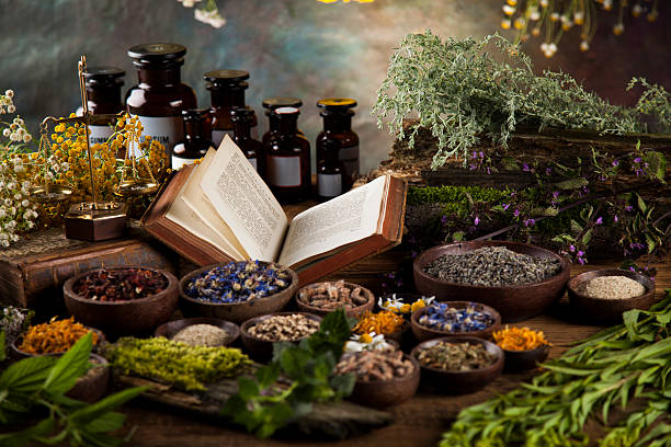 herbal medicine and book on wooden table background - holistic medicine stock photos and pictures