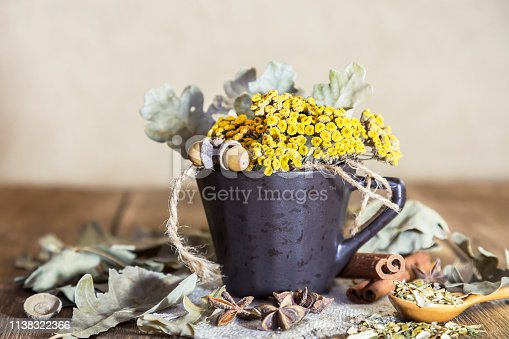 istock Herbal medicine, homeopathy, the collection of medicinal herbs for tea and medicines. Dried tansy flowers and oak leaves in a cup on the background of a wooden table in a rustic style 1138322366