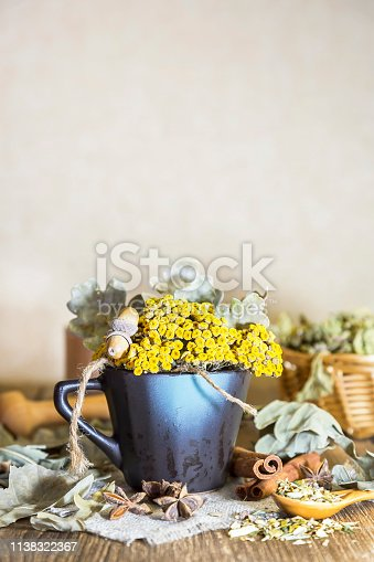 istock Herbal medicine, homeopathy, the collection of medicinal herbs for tea and medicines. Dried tansy flowers and oak leaves in a cup on the background of a wooden table in a rustic style 1138322367