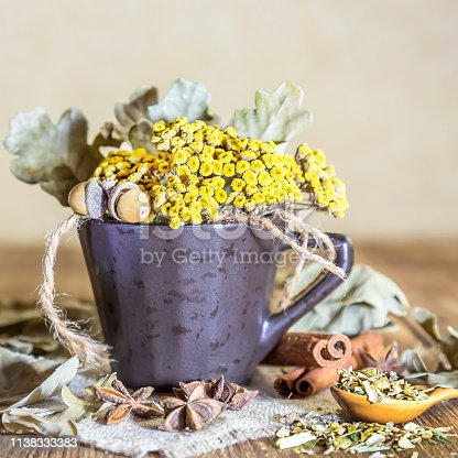 istock Herbal medicine, homeopathy, the collection of medicinal herbs for tea and medicines. Dried tansy flowers and oak leaves in a cup on the background of a wooden table in a rustic style 1138333383