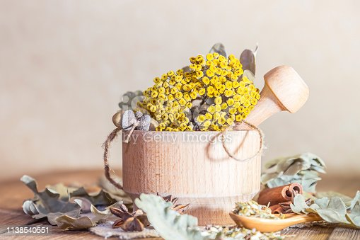 istock Herbal medicine, homeopathy, the collection of medicinal herbs for tea and medicines. Dried tansy flowers and oak leaves in a mortar on a wooden table in a rustic style 1138540551