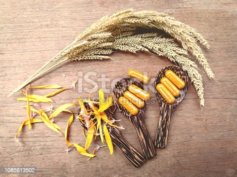 istock Herbal medicine nature Natural Extract turmeric for herb medicine capsules on wooden spoon 1085613502