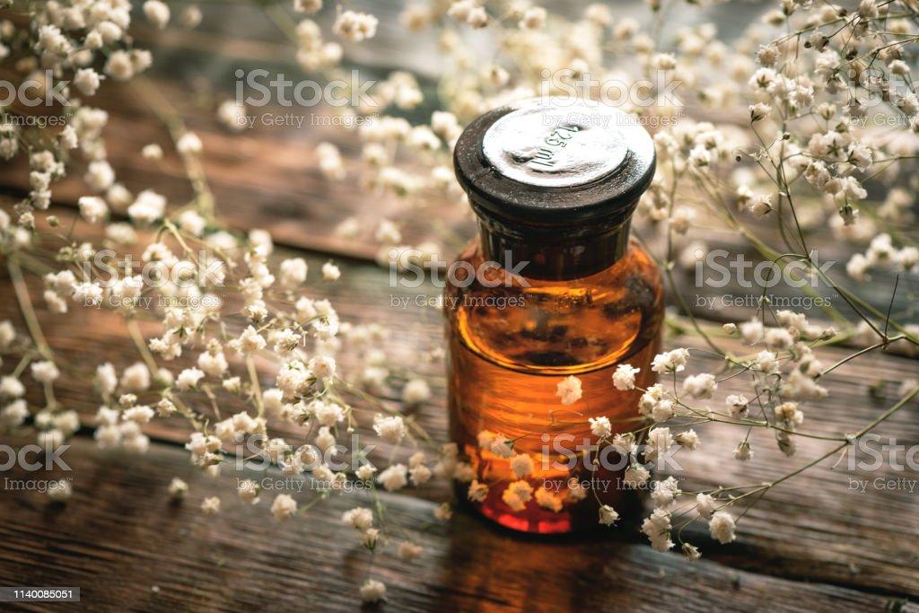 Gypsophila flower essential oil in a bottle on a wooden board...
