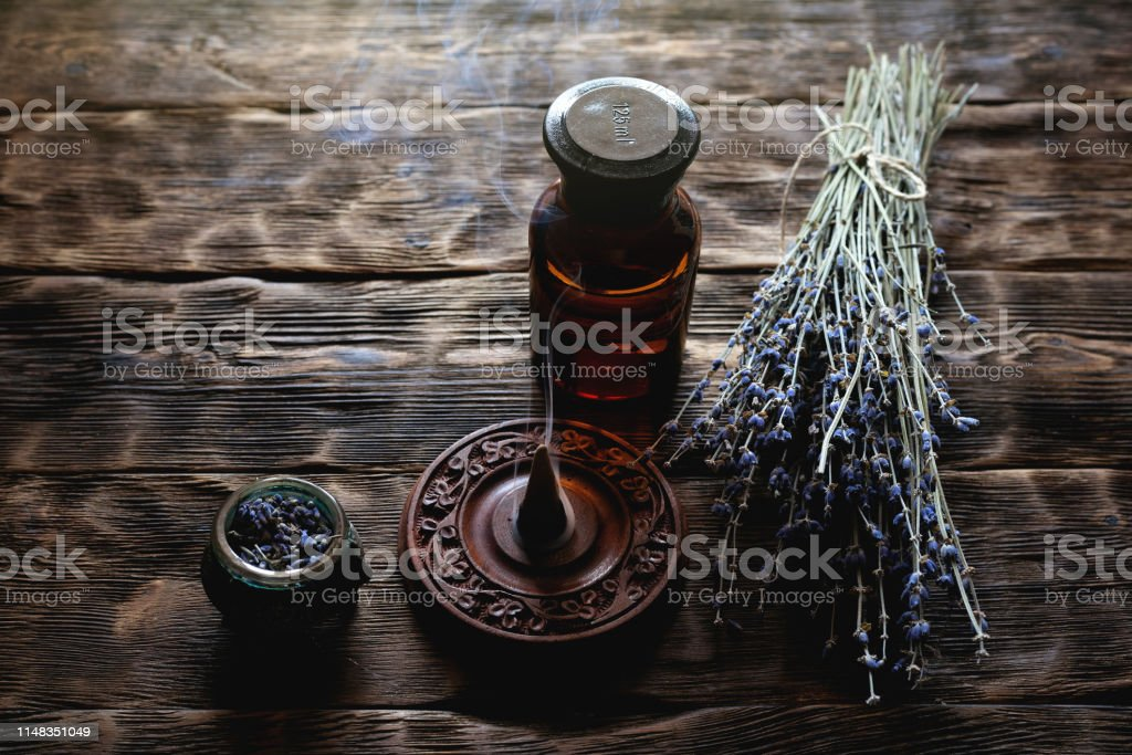 Dried lavender flower branches and lavender essential oil bottles on...