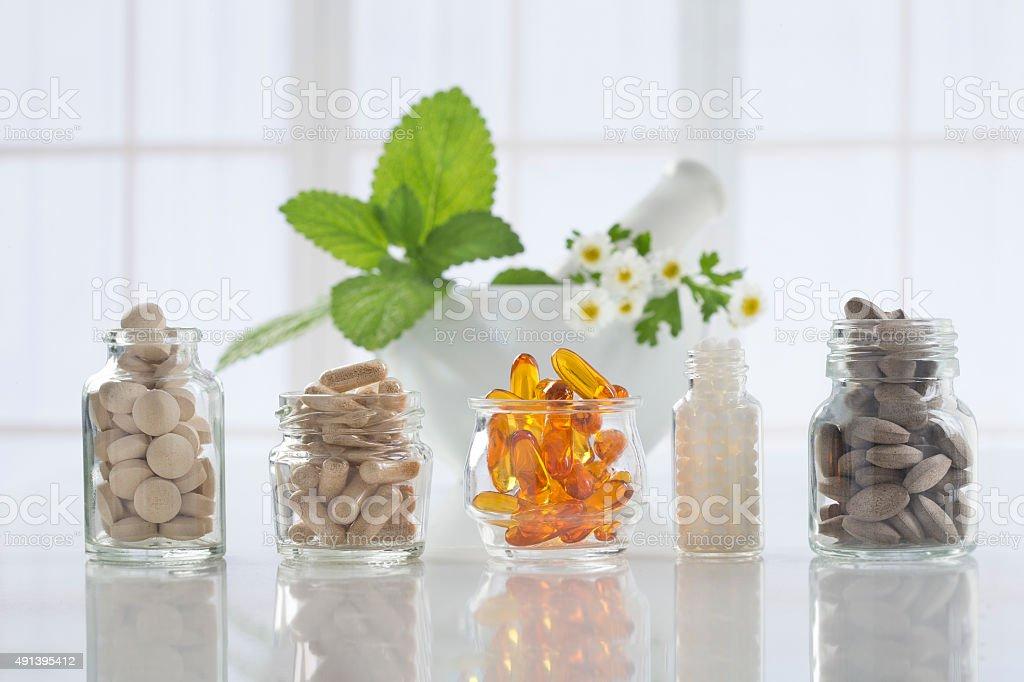 Medicina herbaria pastillas y mortero durante un fondo brillante - foto de stock