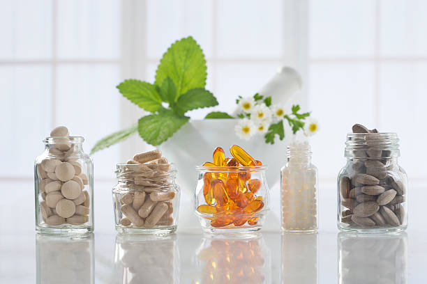 herbal medicine pills and mortar over bright  background - vitamin stock pictures, royalty-free photos & images