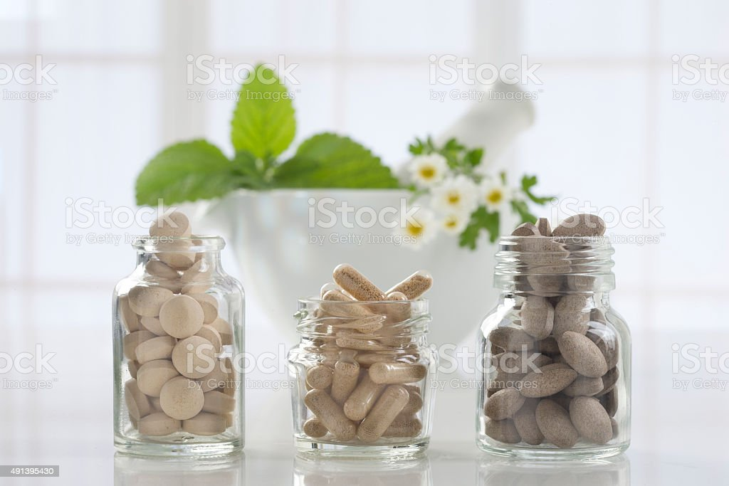 Herbal medicine pills and mortar over bright  background stock photo