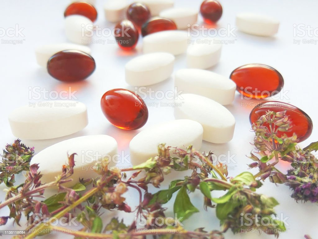 Herbal medicine pills with dry natural herbs on white background....