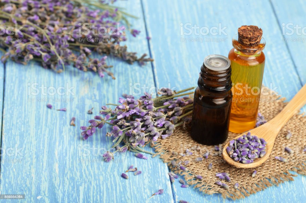 Herbal oil and lavender flowers on wooden background stock photo