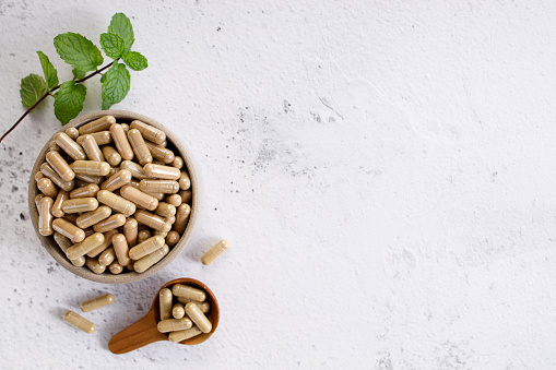 herb capsules, nutritional supplement, in a small bowl on marble background. alternative healthy lifestyle concept.