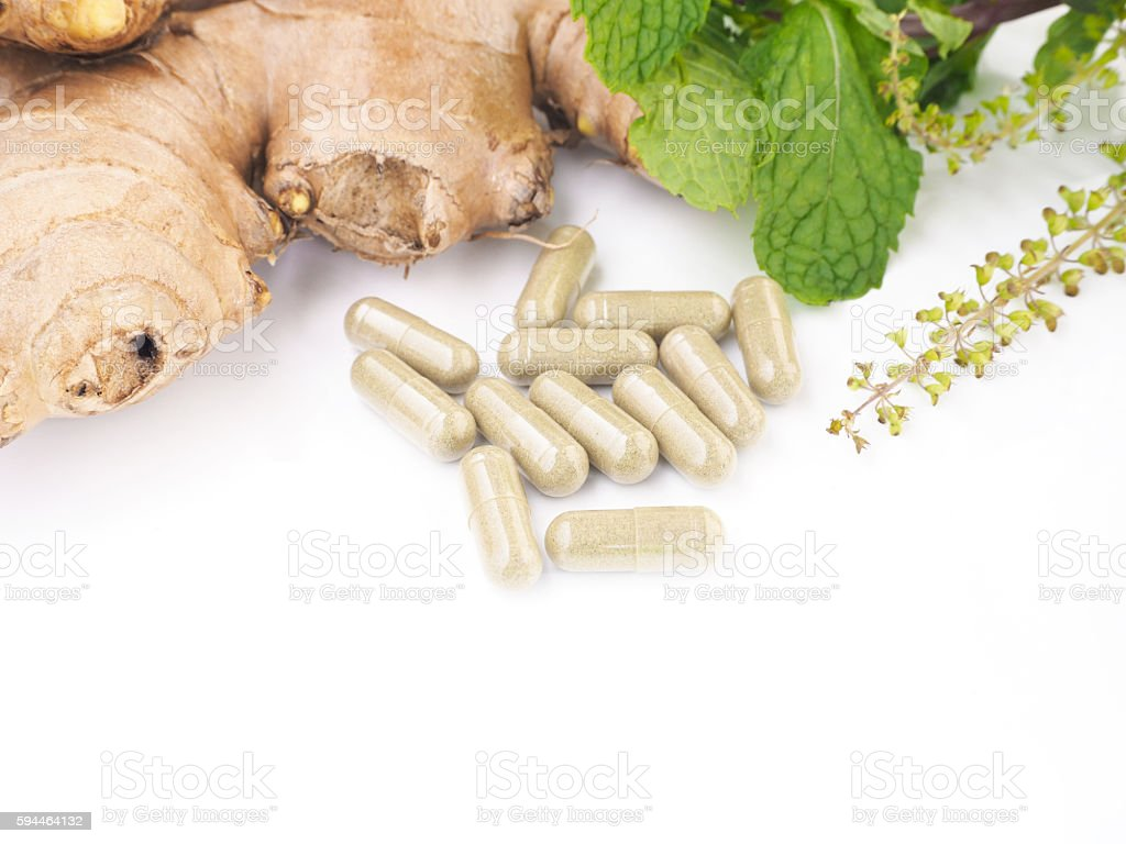 herbal pills with ginger root and green plant stock photo