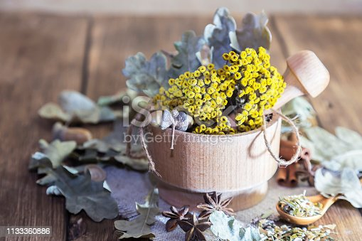 istock Herbal tea. Dried medicinal plant tansy in a wooden mortar, acorns and oak leaves with cinnamon and cardamom for the preparation of medicinal decoctions, drinks from the herbal collection 1133360886