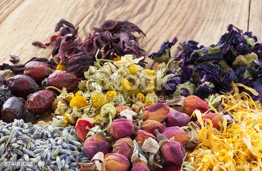 Hibiscus, rose hips, chamomile, mallow, lavender, rose buds ans marigold on wooden background