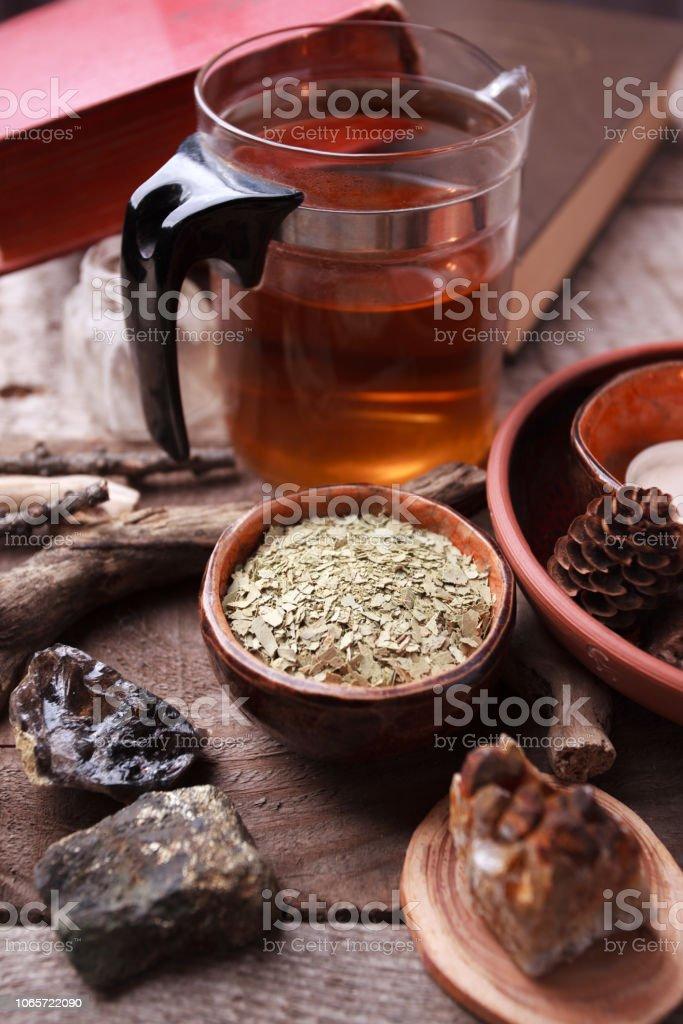 Té de hierbas, homeopatía, medicina alternativa, oculta concepto ritual / seco hojas en la taza de cerámica, piedras, tetera vintage madera fondo, primer plano witchtable - foto de stock
