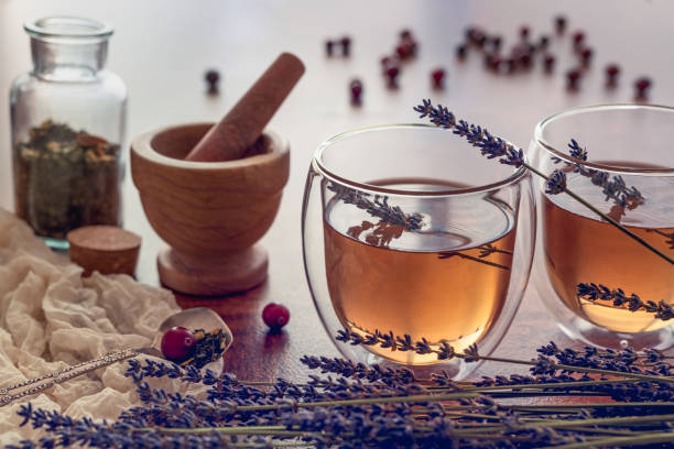 Herbal tea in a glass teacups with lavender and some dry fruits on a wooden kitchen table stock photo