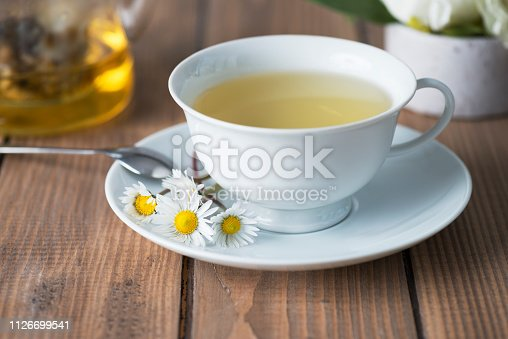 Herbal tea on wooden table with chamomile plants.