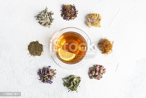 Directly above view of a tea cup with herbal tea and a slice of lemon. Surrounded by a variety of herbal teas  like Chamomile tea, Sage tea, Linden tea, Fennel tea, Melissa tea, Rose tea,  Rosemary Tea and Corn silk tea.