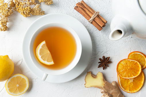 Directly above view of a tea cup with herbal tea and a slice of lemon in it. Surrounded by herbal tea ingredients like chamomile, chamomile tea, lemon, mint leaf, anise, ginger slice, dry orange slices and cinnamon.