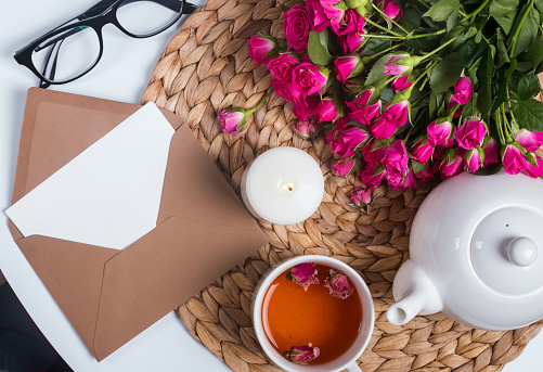 Herbal tea, roses, candle and other objects on the small table, top view