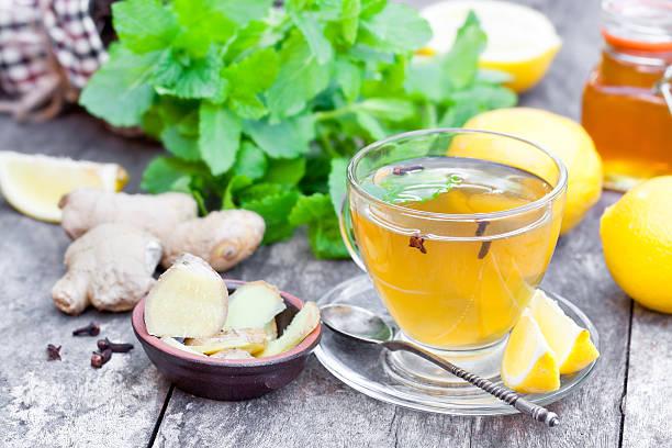 herbal  tea with lemon and ginger on wooden table - ingwerwasser zubereiten stock-fotos und bilder