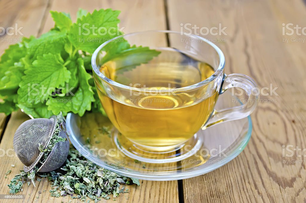Herbal tea with melissa in a cup and strainer - Royalty-free Alternative Therapy Stock Photo