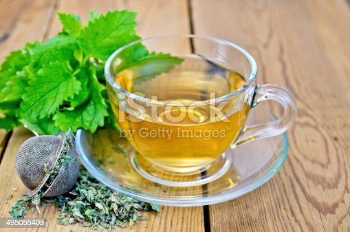 istock Herbal tea with melissa in a cup and strainer 495055405