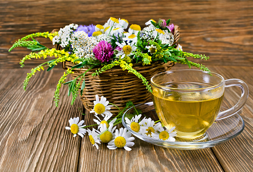 Herbal tea with the chamomile flowers in a glass cup and fresh wild flowers in a basket