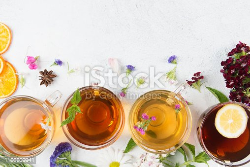 Directly above view of a four tea cups with different herbal teas. Anise, flowers and dried orange slices are spread around the tea cups on white background. One of the teas has a lemon slice.